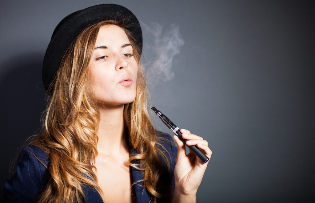 Elegant woman smoking e-cigarette with smoke wearing suit