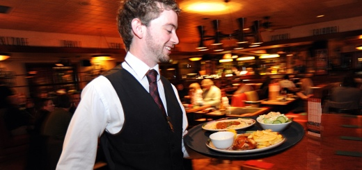 A waiter rushes with a tray of food in a busy restaurant Bradford West Yorkshire.