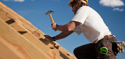 man-with-yellow-hard-hat-and-hammer-on-rooftop